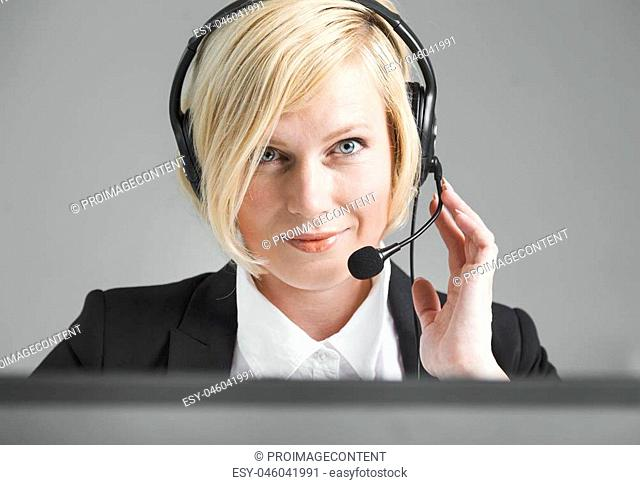 Concentrated call center operator, blonde woman dressed in black jacket and white shirt working on laptop via headset in white office