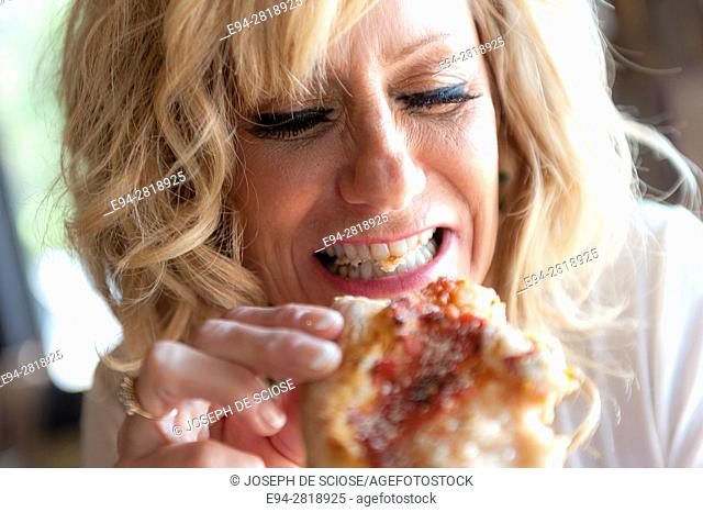 56 year old blond woman playfully eating pizza