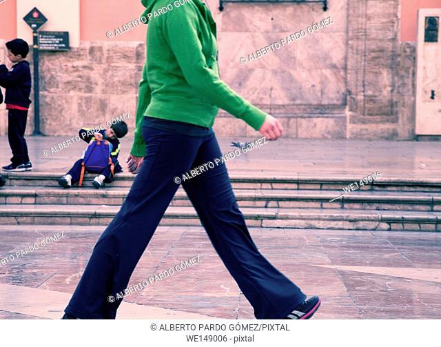 Young woman walking on the street, Plaza de la Virgen, Valencia, Comunidad Valenciana, Spain
