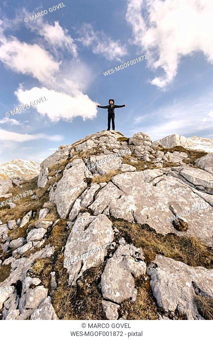 Spain, Asturias, Somiedo, man standing with outstretched arms in mountains