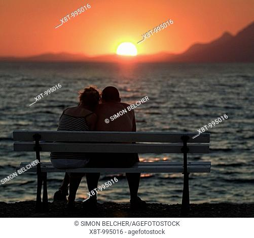 Couple Watching the Sunset over the Mediterranean Ocean