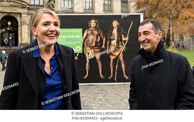 Gruene chairmen Simone Peter (l) and Cem Oezdemir (r) standing in front of the newly unveiled poster reading 'Eure Klimapolitik ist steinalt' (lit