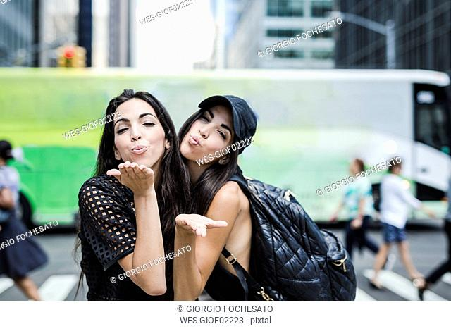 USA, New York City, two twin sisters blowing a kiss in Manhattan