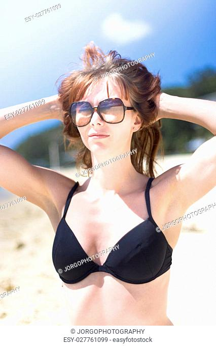 Half Body Portrait Of Young Woman Relaxing On Beach With Sunglasses And Bikini Top With Blue Sky Background