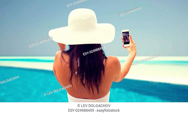 lifestyle, leisure, summer, technology and people concept - smiling young woman or teenage girl in sun hat taking selfie with smartphone over beach and swimming...