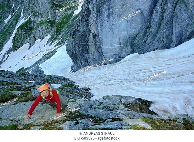 Woman climbing through rocky terrain, snowgully in background, Sentiero Roma, Bergell range, Lombardy, Italy