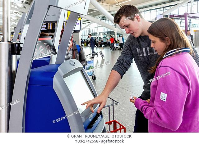 A Young Couple Check In and Print Out Their Boarding Passes, Heathrow Airport, London, UK