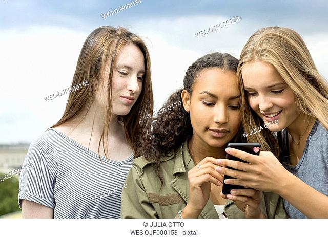 Three teenage girls on roof top looking at cell phone
