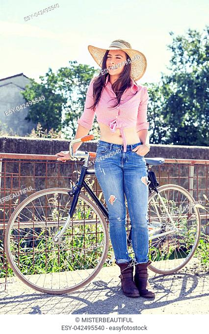 pretty young woman on bike in a country road