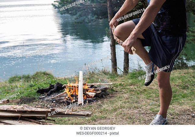 Bulgaria, Man breaking wood for camp fire at lakeshore