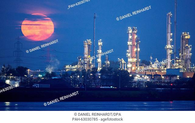 The red full moon sets behind the Holborn oil refinery in the port of Hamburg, Germany, 27 October 2015. PHOTO: DANIEL REINHARDT/DPA | usage worldwide