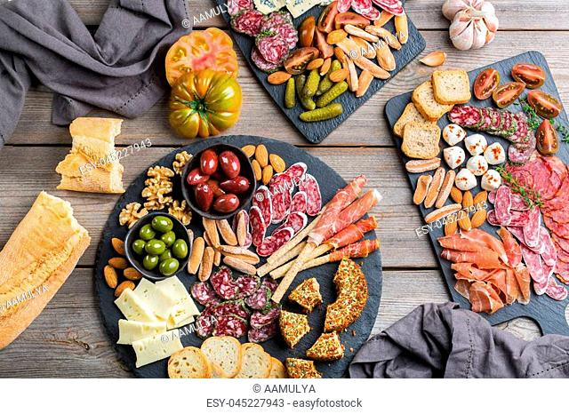 Still life, food and drink, holidays concept. Assortment of spanish tapas or italian antipasti with meat, ham, olives, cheese, nuts and bread on a table