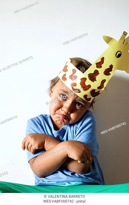 Portrait of smiling little boy wearing self-made headdress pulling funny faces