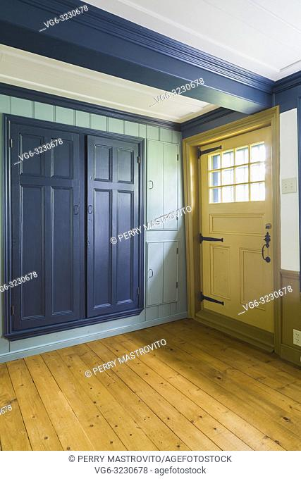 Yellow painted wooden rear entrance door with glass pane window and blue closet doors in living room with spruce wood floorboards inside an old 1809 French...