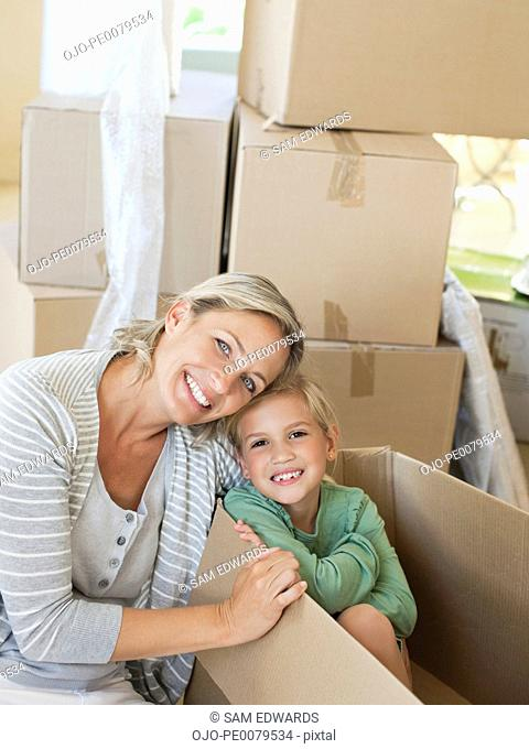Mother and son sitting with moving boxes