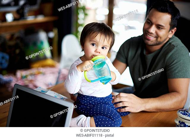 Portrait of baby girl sitting on table drinking water at home with father in background