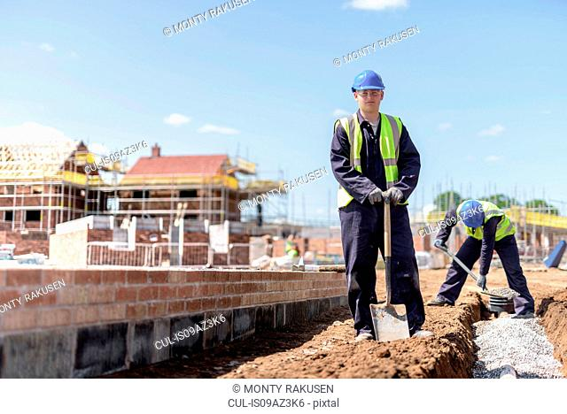 Portrait of apprentice builder laying pipework on housing building site