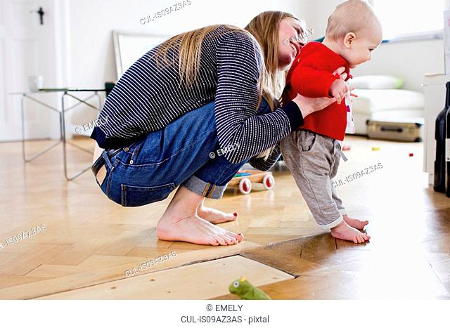 Mid adult woman holding baby daughter to take first steps