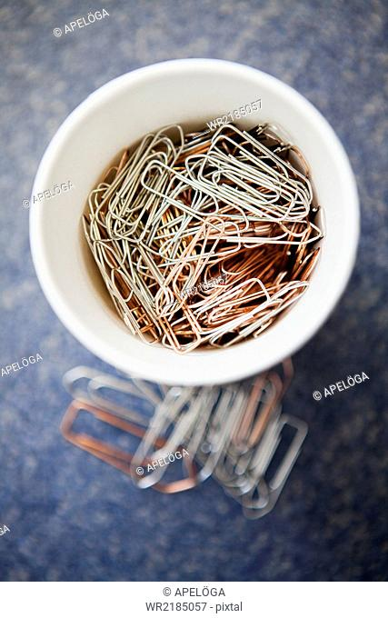 Close-up of a container filled with paper clips