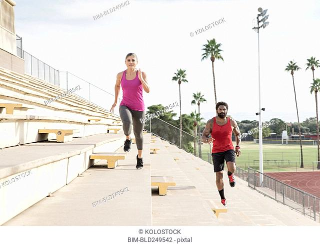 Man and woman running on bleachers