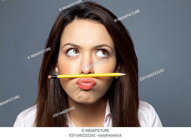 Female executive balancing pencil on lip