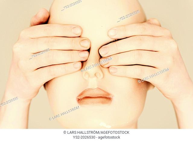 Head of mannequin with human hands covering the eyes