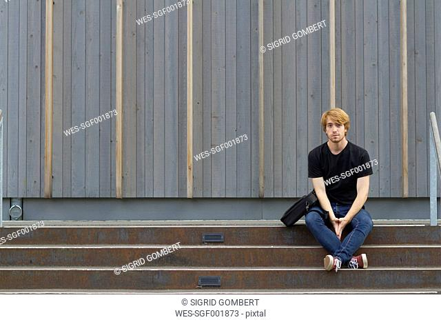 Young man sitting on steps in front of wooden facade