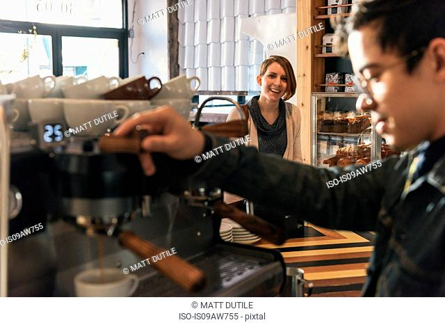 Waiter pouring coffee from coffee machine in cafe
