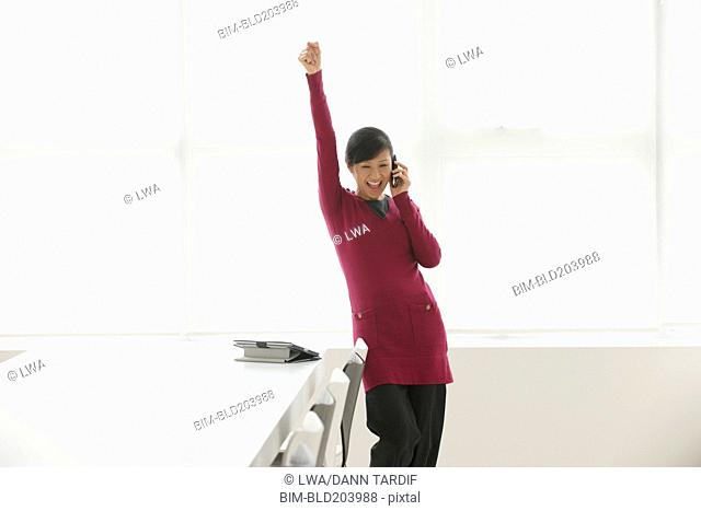 Chinese businesswoman cheering in office