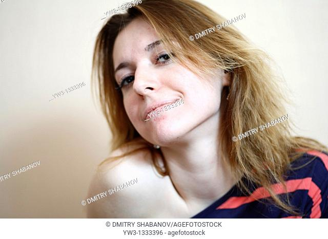 pretty girl against light wall blank expression