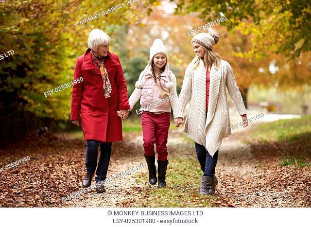 Female Multl Generation Family Walking Along Autumn Path