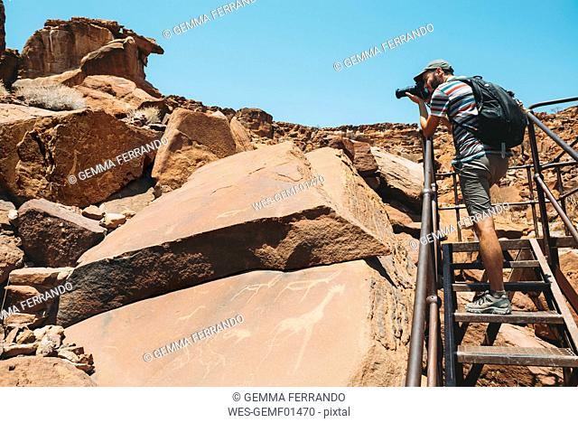 Namibia, Damaraland, Twyfelfontein, Man taking pictures of petroglyphs
