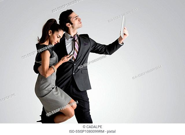 Man using digital tablet, woman on cell phone