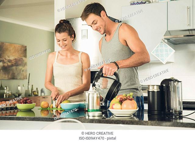 Young couple preparing a coffee and fruit breakfast at kitchen counter