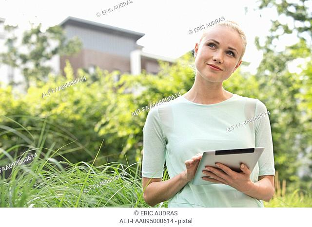 Young woman using digital tablet outdoors