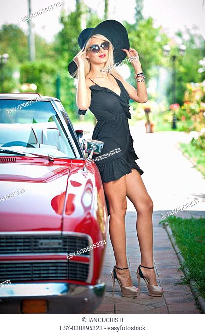Summer portrait of stylish blonde vintage woman with long legs posing near red retro car. fashionable attractive fair hair female with black hat near a red...