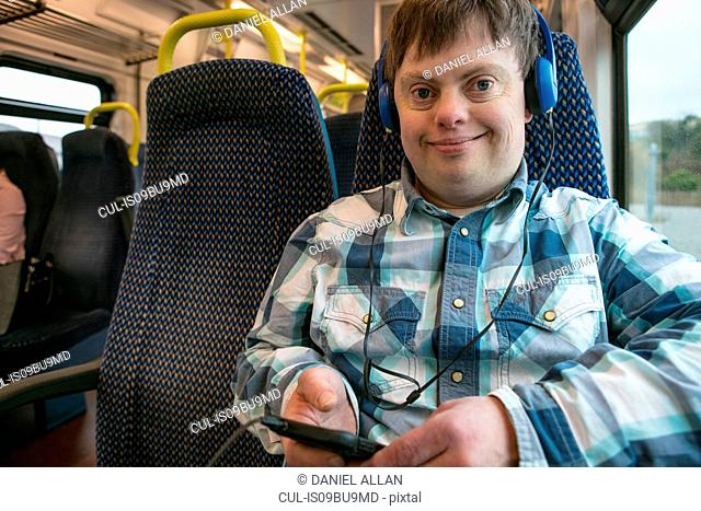 Man with down syndrome with using headphones and cell phone on train