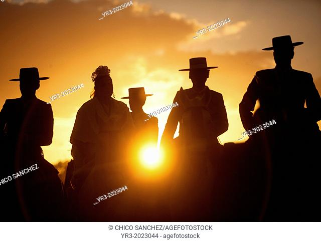 Pilgrims wearing Spanish hats ride their horses at sunset during the pilgrimage to the shrine of the Virgin of Rocio, in Almonte, Donana National Park