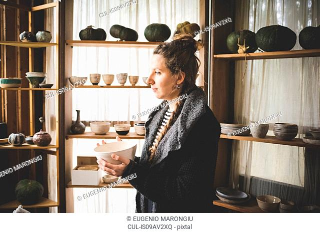 Side view of young woman holding ceramic dish in front of shelves displaying clay pots and pumpkins