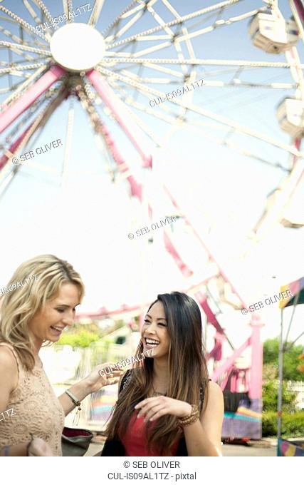 Two women standing in front of feris wheel, laughing