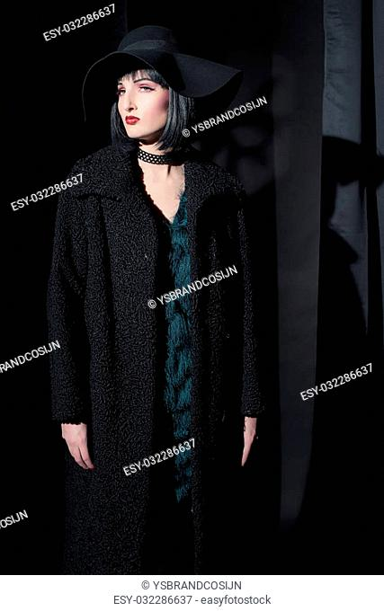 Gothic fashion woman wearing black coat and hat