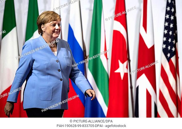 28 June 2019, Japan, Osaka: Chancellor Angela Merkel (CDU) comes to the welcoming ceremony of the G20 summit. The heads of state and government of the 19...