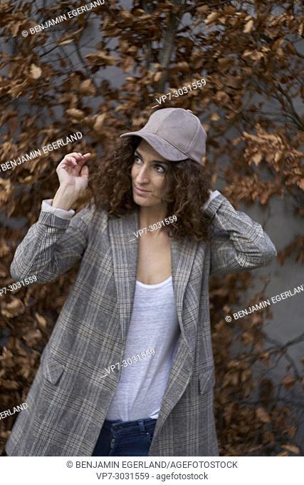 thoughtful multi-cultural mature woman against autumn leaves. Fashion blogger Aslihan Kiratli. Half German and half Turkish ethnicity