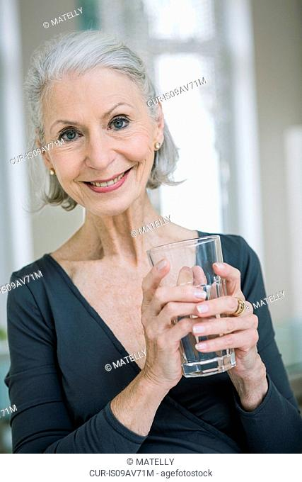 Portrait of gray haired senior woman holding tumbler looking at camera smiling