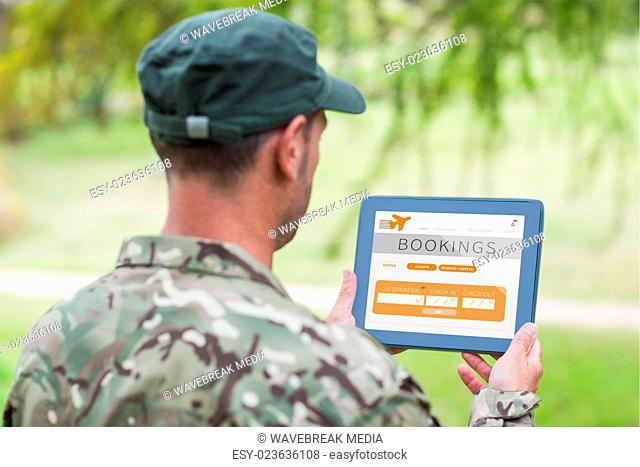 Composite image of army man using tablet