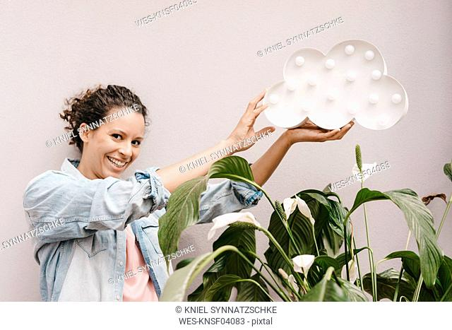 Smiling woman holding cloud over house plant