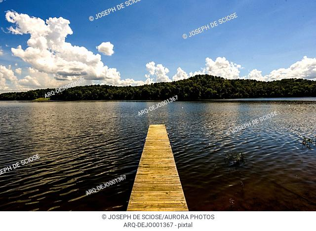 Small dock jutting into calm lake with hills and clouds in distance