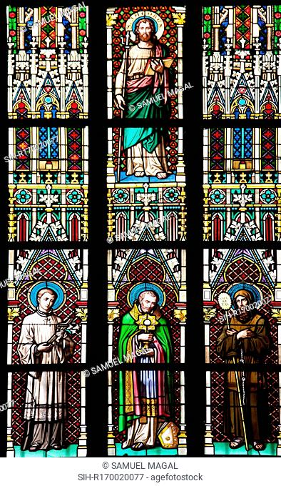 Stained Glass Window depicting St. Jacobus Holding a Cane and a Book. Below are, from left to right, the three standing figures of St Aloysius