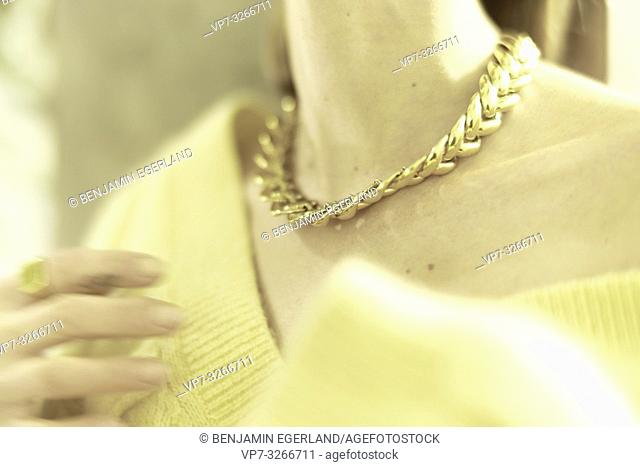 wealthy aristocratic woman wearing golden multi-chain necklace around neck, in Munich, Germany