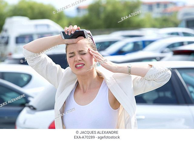 Woman in car park with mobile phone, headache